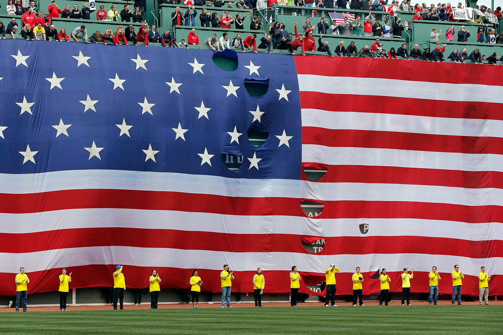 . Boston Marathon volunteers stand beneath a giant flag on the outfield wall during a tribute to victims of the Boston Marathon bombings, before a baseball game between the Boston Red Sox and the Kansas City Royals in Boston, Saturday, April 20, 2013. (AP Photo/Michael Dwyer)