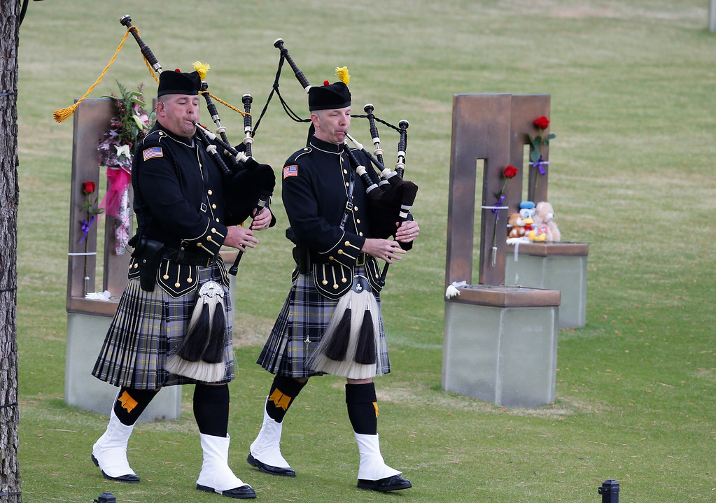 . Bagpipers walk through the Field of Empty Chairs at the Oklahoma City National Memorial at the start of ceremonies to commemorate the 20 year anniversary of the Oklahoma City bombing in Oklahoma City, Sunday, April 19, 2015. (AP Photo/Sue Ogrocki)