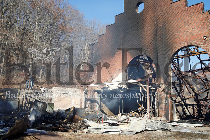 Tenants of the glass factory look over the ruins of the burnt out building Saturday. The Friday night fire rekindled Saturday morning destroying a secondary building (left) next to the original structure.  Seb Foltz/Butler Eagle