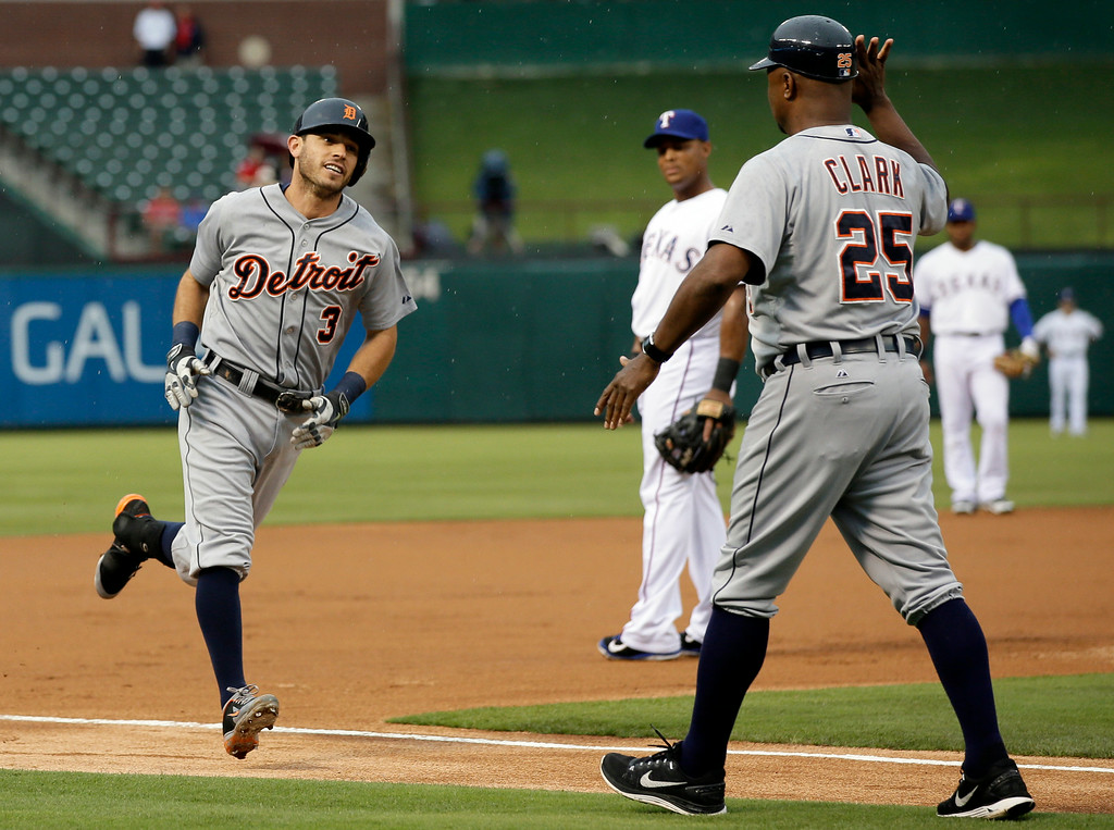 . Detroit Tigers\' Ian Kinsler (3) rounds third as Dave Clark (25) congratulates him on his solo home run that came off a pitch from Texas Rangers\' Colby Lewis in the first inning of a baseball game, Tuesday, June 24, 2014, in Arlington, Texas.The game is the first appearance by Kinsler in the ballpark since being traded to the Tigers for Prince Fielder. Rangers third baseman Adrian Beltre watches from the rear. (AP Photo/Tony Gutierrez)