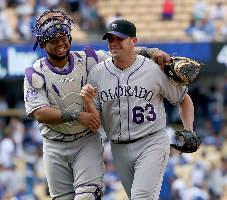 . Closer Rafael Betancourt #63 and catcher Wilin Rosario #20 of the Colorado Rockies celebrate after Betancourt got the final out and picked up the save against the Los Angeles Dodgers at Dodger Stadium on July 14, 2013 in Los Angeles, California.  The Rockies won 3-1.  (Photo by Stephen Dunn/Getty Images)