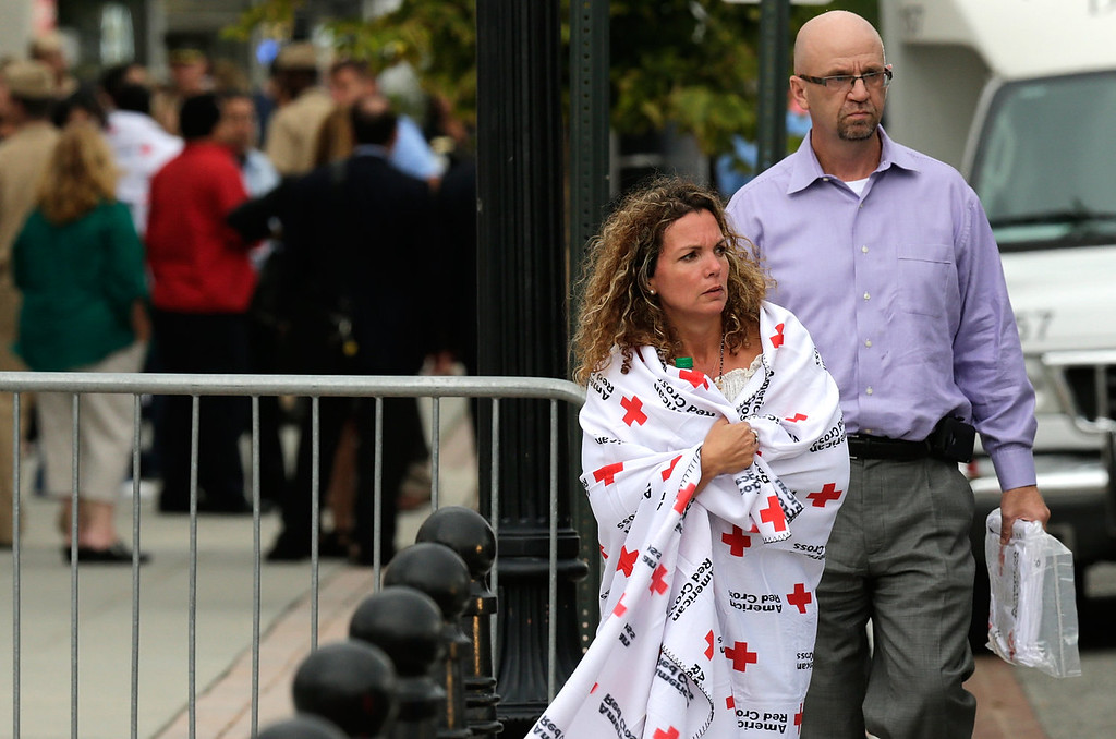 . A woman wrapped in a Red Cross blanket leaves a gathering point for reuniting family members of Navy Yard employees that was set up inside Nationals Park in the wake of the shooting September 16, 2013 in Washington, DC. Police believe at least one gunman shot and killed at least 12 people and wounded others in an incident that put parts of the city on lockdown. (Photo by Win McNamee/Getty Images)