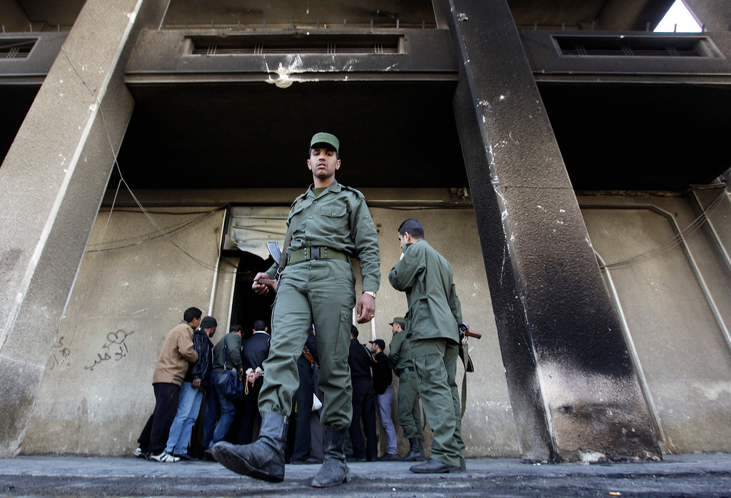""". A Syrian army soldier steps out from the burned court building that was set on fire by Syrian anti-government protesters, in the southern city of Daraa, Syria, on Monday March 21, 2011. Mourners chanting \""""No more fear!\"""" have marched through a Syrian city where anti-government protesters had deadly confrontations with security forces in recent days. The violence in Daraa, a city of about 300,000 near the border with Jordan, was fast becoming a major challenge for President Bashar Assad, who tried to contain the situation by freeing detainees and promising to fire officials responsible for the violence. (AP Photo/Hussein Malla)"""