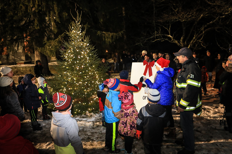 Kingston firefighter Chris Verracka, organizer of the activities on the Town Green for the Luminaries event, looks on as his children Dylan, in red coat, and Jessica, blue coat, flip the switch to turn on the Christmas Tree lights. Wicked Local Photo/Denise Maccaferri