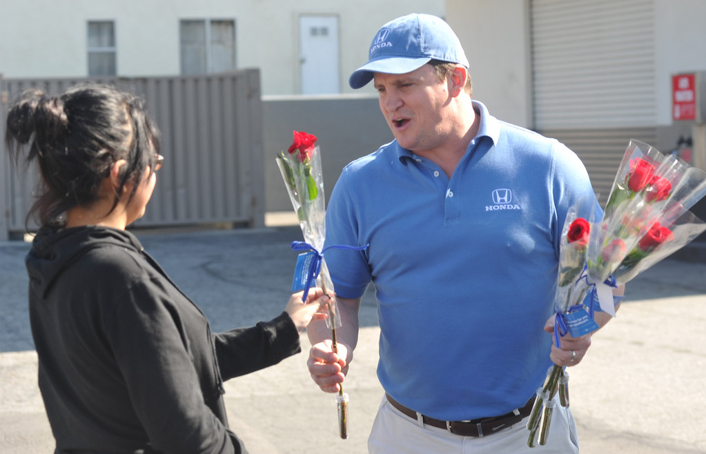 . Steve Judkins, with Honda, gives Jazal Ibanez a long-stem red rose on Valentine\'s Day at Merill Gardens in Whittier on Thursday February 14, 2013. The Helpful Guys in Blue, a group sponsored by the Southern California Honda Dealers Association surprise Whittier residents with a complimentary red roses. (SGVN/Staff Photo by Keith Durflinger)