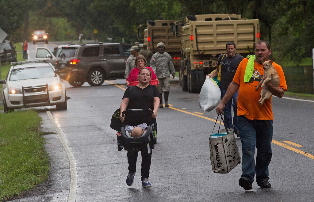 . People arrive to be evacuated by members of the Louisiana Army National Guard near Walker, La., after heavy rains inundating the region, Sunday, Aug. 14, 2016. (AP Photo/Max Becherer)