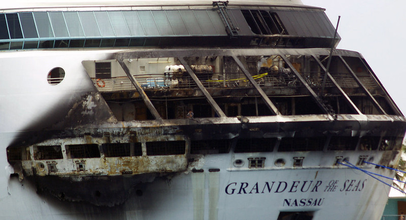 . The fire-damaged exterior of Royal Caribbean\'s Grandeur of the Seas cruise ship is seen while docked in Freeport, Grand Bahama island, Monday, May 27, 2013. Royal Caribbean said the fire occurred early Monday while on route from Baltimore to the Bahamas on the mooring area of deck 3 and was quickly extinguished. All 2,224 guests and 796 crew were safe and accounted for. (AP Photo/The Freeport News, Jenneva Russell)