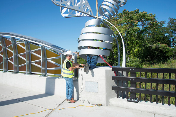 09/03/19 Wesley Bunnell | Staff The final bee statue was hoisted into place onto the Bee Hive Bridge by Sign Pro on Tuesday September 3, 2019. Install Manager Rob Mulcunry, L, assists Spencer Brown as he bolts the statue into place.