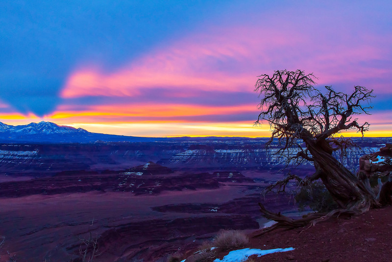 """I haven't had much luck with sunrises in the vicinity of Canyonlands National Park. The skies stayed white and overcast for much of the """"golden hour"""" during my visit to Dead Horse Point State Park just outside of Canyonlands' Island in the Sky district, but I did manage to capture a bit of color as sun fought through from beyond the La Sal mountains in the distance."""