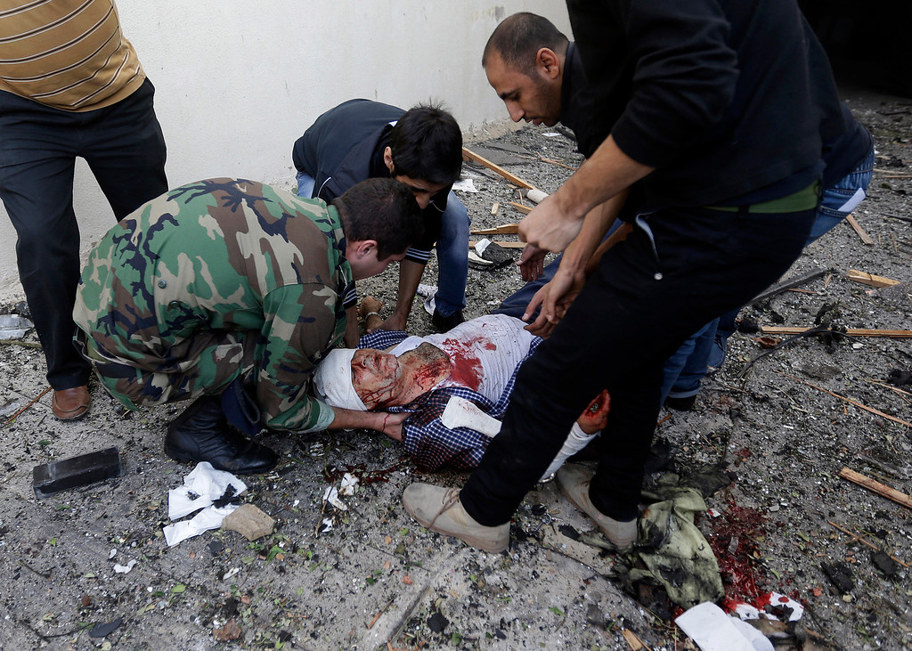 . A Lebanese soldier and citizens help an injured man on the ground, at the scene where two explosions have struck near the Iranian Embassy killing many, in Beirut, Lebanon, Tuesday Nov. 19, 2013.  (AP Photo/Hussein Malla)