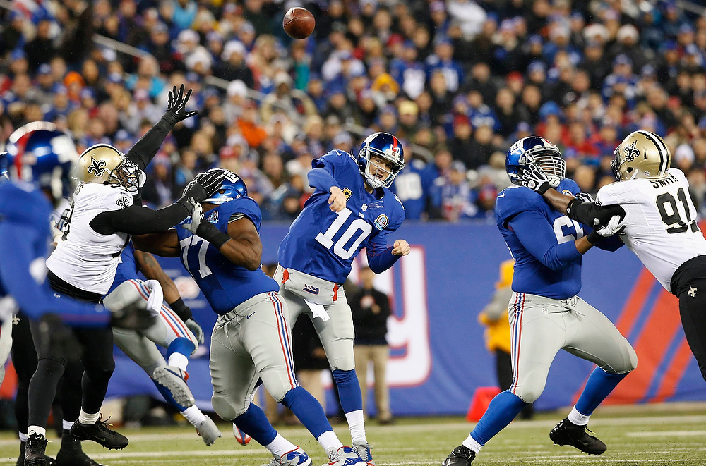 Description of . New York Giants quarterback Eli Manning (10) throws a pass during the third quarter against the New Orleans Saints in their NFL football game in East Rutherford, New Jersey, December 9, 2012. REUTERS/Mike Segar