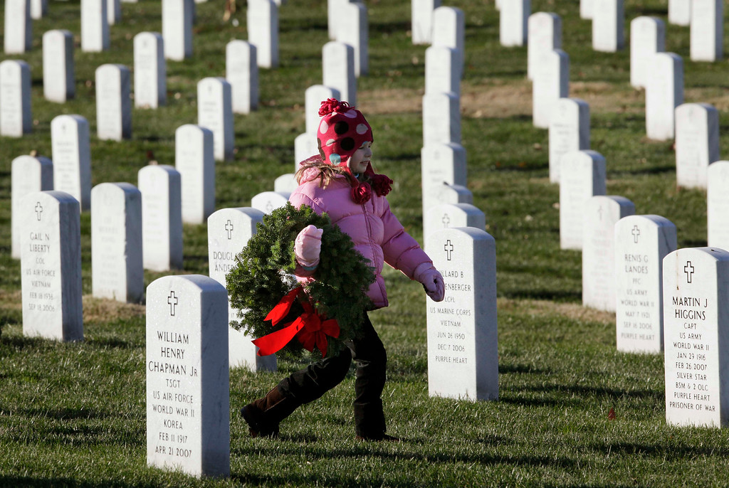 . Emily Mead, 6, of Great Falls, Va., walks to her relative\'s grave in with a wreath as part of Wreaths Across America in Section 60 at Arlington National Cemetery in Arlington, Va., Saturday, Dec. 12, 2009. More than 16,000 wreaths were placed at graves throughout the cemetery. (AP Photo/Alex Brandon)