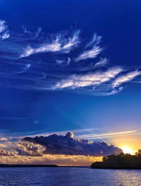 Wispy white Cirrus and dark Cumulonimbus clouds in a seascape sunrise Sunrise. Kaurie Creek, The Sandy Straits, Queensland, Australia.