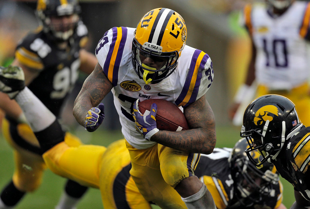 . LSU running back Jeremy Hill (33) rushes through the Iowa defense, including defensive back Desmond King, right, to score on a 14-yard touchdown run during the second quarter of the Outback Bowl NCAA college football game Wednesday, Jan. 1, 2014, in Tampa, Fla. (AP Photo/Chris O\'Meara)