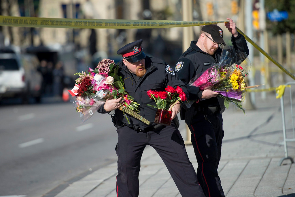 . Ottawa Police officers move flowers to an area in front of the National War Memorial near Parliament Hill , where Cpl. Nathan Cirillo, 24, was killed by a gunman in Ottawa on Thursday, Oct. 23, 2014.  Michael Zehaf Bibeau fatally shot  Cirillo on Wednesday, at the National War Memorial before setting his sights on Parliament Hill. Bibeau was killed just feet from where hundreds of MPs were meeting for their weekly caucus meetings.  (AP Photo/The Canadian Press, Justin Tang)