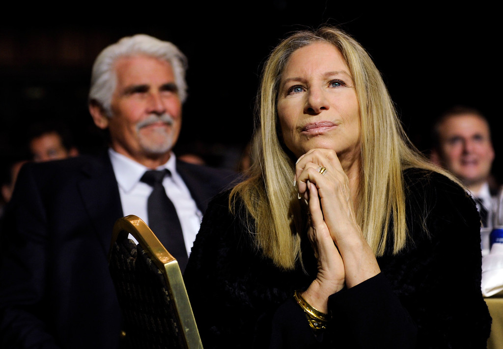 . Barbra Streisand listens to President Barack Obama speak at the USC Shoah Foundation�s 20th anniversary Ambassadors for Humanity gala in Los Angeles, Wednesday, May 7, 2014. Streisand\'s husband, James Brolin, sits at left. (AP Photo/Susan Walsh)