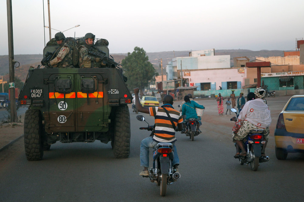Description of . A motorcyclist waves his support as French troops in two armored personnel carriers drive through Mali's capital Bamako on the road to Mopti Tuesday Jan. 15, 2013. French forces led an all-night aerial bombing campaign Tuesday to wrest control of a small Malian town from armed Islamist extremists who seized the area, including its strategic military camp. A a convoy of 40 to 50 trucks carrying French troops crossed into Mali from Ivory Coast as France prepares for a possible land assault. Several thousand soldiers from the nations neighboring Mali are also expected to begin arriving in coming days. (AP Photo/Jerome Delay)