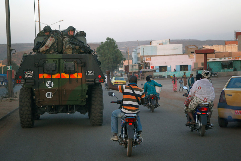 . A motorcyclist waves his support as French troops in two armored personnel carriers drive through Mali\'s capital Bamako on the road to Mopti Tuesday Jan. 15, 2013. French forces led an all-night aerial bombing campaign Tuesday to wrest control of a small Malian town from armed Islamist extremists who seized the area, including its strategic military camp. A a convoy of 40 to 50 trucks carrying French troops crossed into Mali from Ivory Coast as France prepares for a possible land assault. Several thousand soldiers from the nations neighboring Mali are also expected to begin arriving in coming days. (AP Photo/Jerome Delay)