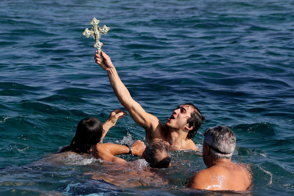 . A swimmer holds up the cross after it was thrown from an Orthodox priest into the water, during an epiphany ceremony to bless the sea waters at Famagousta or Varosia beach in the Turkish Cypriots breakaway north part of the eastern Mediterranean divided island of Cyprus, Friday, Jan 6, 2017. Many Orthodox Christian faithful attended the Epiphany Day blessing of the waters in Famagusta in Cyprus\', the second time the ceremony has taken place since 1974 when the small island nation was cleaved along ethnic lines. (AP Photo/Petros Karadjias)