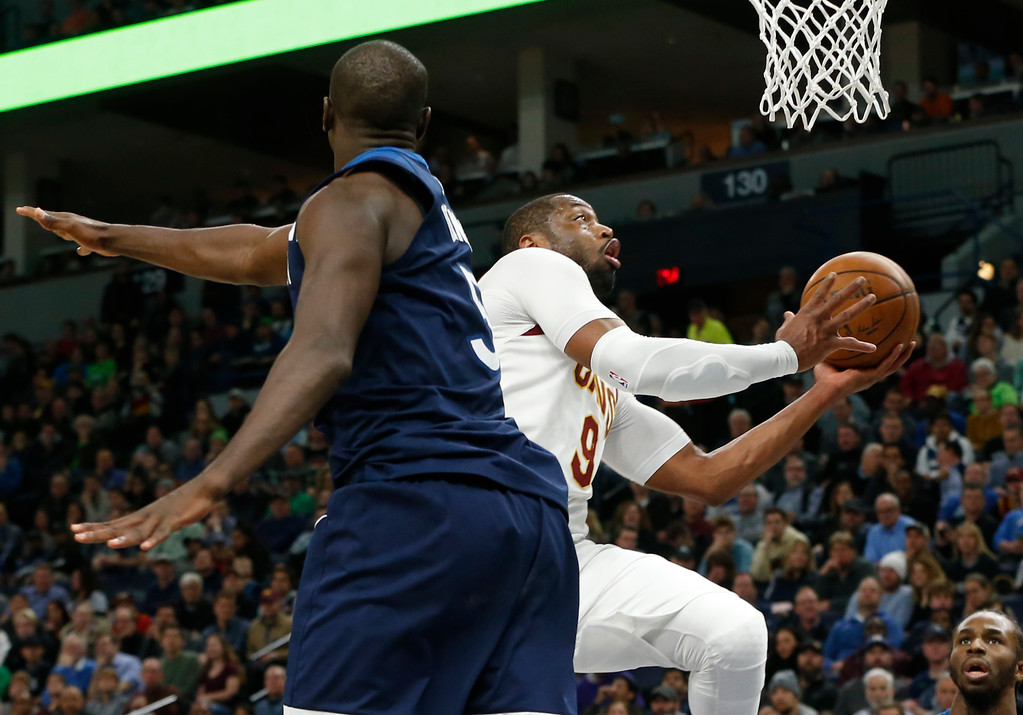 . Cleveland Cavaliers\' Dwyane Wade, right, lays up in front of Minnesota Timberwolves\' Gorgui Dieng, of Senegal, in the second half of an NBA basketball game Monday, Jan. 8, 2018, in Minneapolis. (AP Photo/Jim Mone)