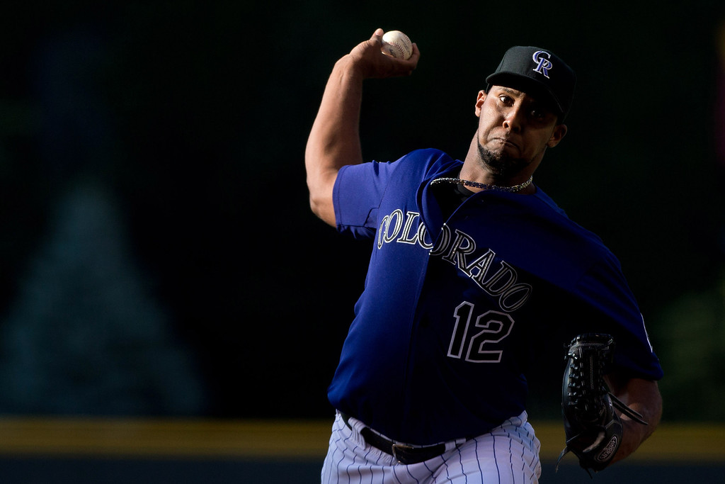 . DENVER, CO - JULY 20:  Starting pitcher Juan Nicasio #12 of the Colorado Rockies delivers to home plate during the first inning against the Chicago Cubs at Coors Field on July 20, 2013 in Denver, Colorado.  (Photo by Justin Edmonds/Getty Images)