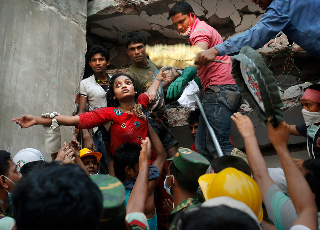 Description of . A Bangladeshi woman survivor is lifted out of the rubble by rescuers at the site of a building that collapsed Wednesday in Savar, near Dhaka, Bangladesh, Thursday, April 25, 2013. The collapse of Rana Plaza in Dhaka that killed 1,129 people. (AP Photo/Kevin Frayer)