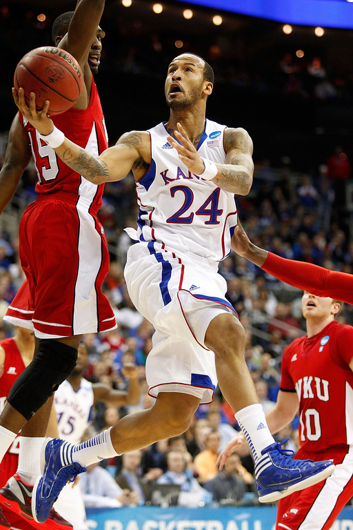 . KANSAS CITY, MO - MARCH 22: Travis Releford #24 of the Kansas Jayhawks shoots against O\'Karo Akamune #15 and Caden Dickerson #10 of the Western Kentucky Hilltoppers in the first half during the second round of the 2013 NCAA Men\'s Basketball Tournament at the Sprint Center on March 22, 2013 in Kansas City, Missouri.  (Photo by Ed Zurga/Getty Images)