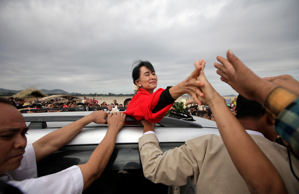 . Myanmar pro-democracy leader Aung San Suu Kyi shakes hands with supporters after giving a speech in Monywa November 30, 2012. Suu Kyi offered to mediate between company officials and those who are opposing a vast copper mining project after riot police fired water cannon and tear gas on Thursday to break up a three-month protest against the project run by the powerful Myanmar military and its partner, a subsidiary of a Chinese arms manufacturer. Activists said at least 50 people had been injured and 23 were in hospital, some suffering burns after incendiary devices were hurled into their camps by police.  REUTERS/Soe Zeya Tun