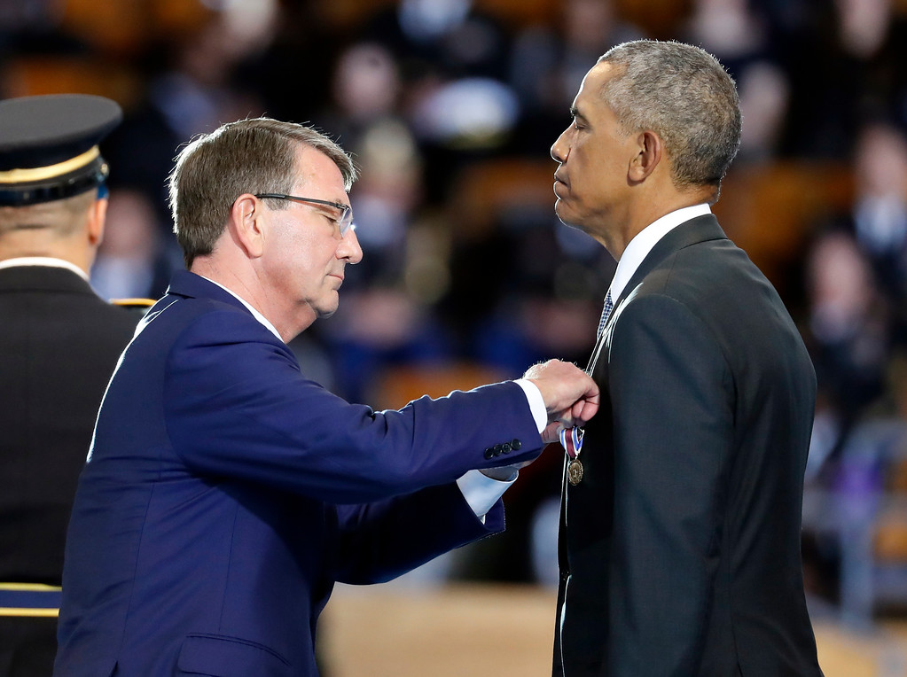 . Defense Secretary Ash Carter pins the Department of Defense for Distinguished Public Service on President Barack Obama during an Armed Forces Full Honor Farewell Review for the president, Wednesday, Jan. 4, 2017, at Conmy Hall, Joint Base Myer-Henderson Hall, Va. (AP Photo/Alex Brandon)
