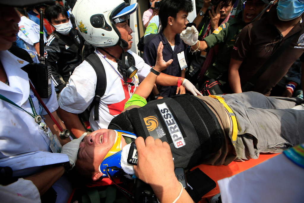 . An injured foreign reporter is carried by medic team to an ambulance during a clash between police force and anti-government protesters Tuesday, Feb. 18, 2014 in Bangkok, Thailand.  (AP Photo/Wason Wanichakorn)