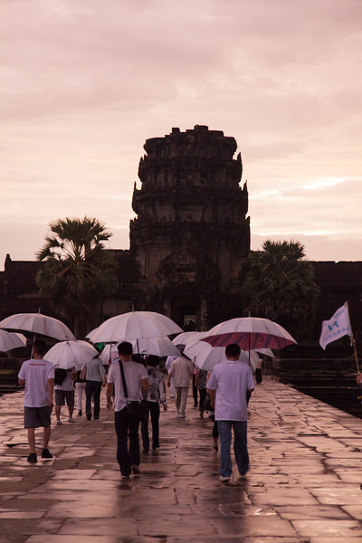 Tourists with matching umbrellas stream into Angkor Wat at sunrise.