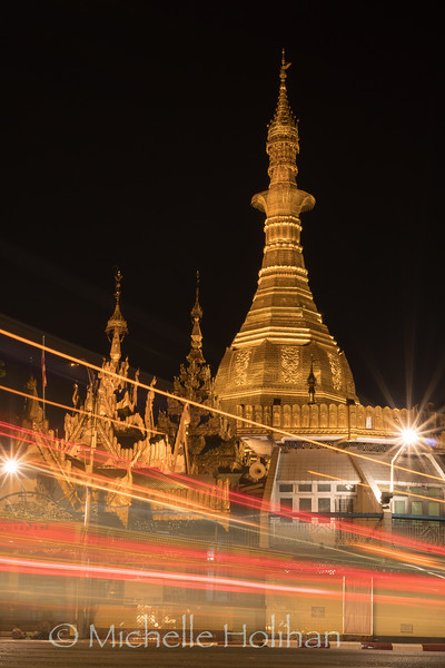 Traffic lights streak in front of the golden Sule Pagoda at night in Yangon, Myanmar