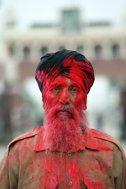 . A Sikh worker is smeared in color by Indian Border Security Force (BSF) soldiers (unseen) during the Holi Festival at the India-Pakistan Joint Check Post (JCP) at the Attari border, some 30 kms from Amritsar, India, 17 March 2014. Holi is celebrated at the end of the winter season on the last full moon day of the lunar month Phalguna (February or March) which usually falls in the later part of February or March and main day is celebrated by people throwing colored powder and colored water at each other.  EPA/RAMINDER PAL SINGH