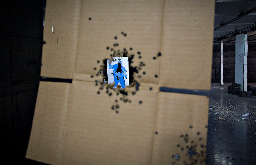 . A target hit several times is seen through a piece of cardboard, also peppered with bullet holes, at the DVC Indoor Shooting Centre in Port Coquitlam, British Columbia March 22, 2013. The DVC is the only indoor shooting centre in the province that rents firearms to the public without a license. Canada has very strict laws controlling the use of handguns and violent crime is relatively rare. Picture taken March 22, 2013.  REUTERS/Andy Clark