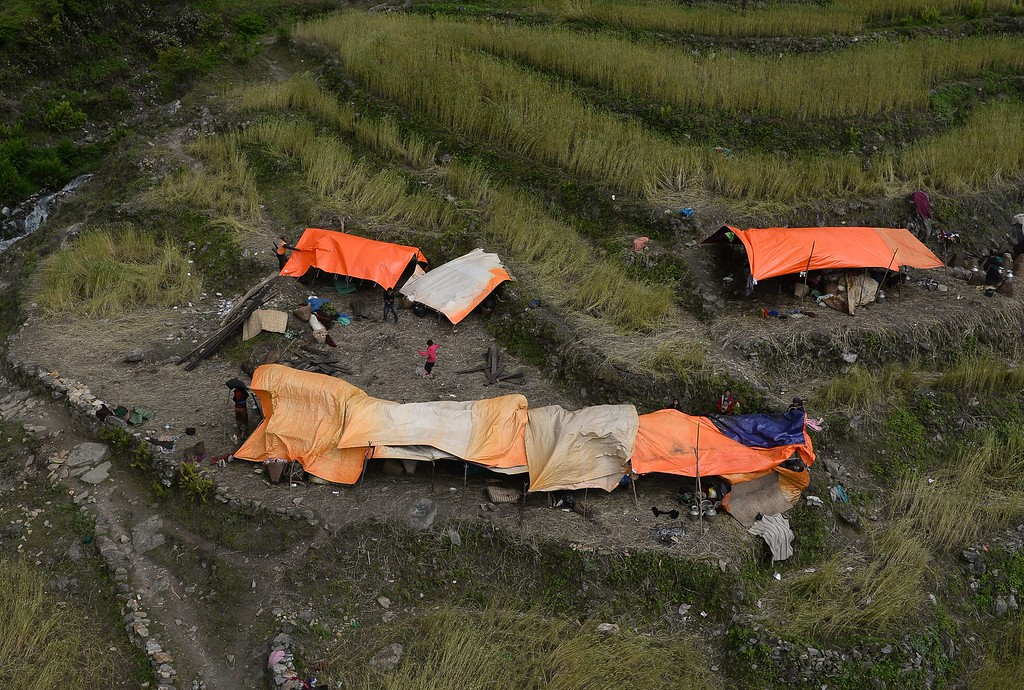 . Nepalese villagers gather at their makeshift tents at Uiya village, in northern-central Gorkha district on April 29, 2015.   Hungry and desperate villagers rushed towards relief helicopters in remote areas of Nepal, begging to be airlifted to safety, four days after a monster earthquake killed more than 5,000 people.    AFP PHOTO / SAJJAD  HUSSAIN/AFP/Getty Images
