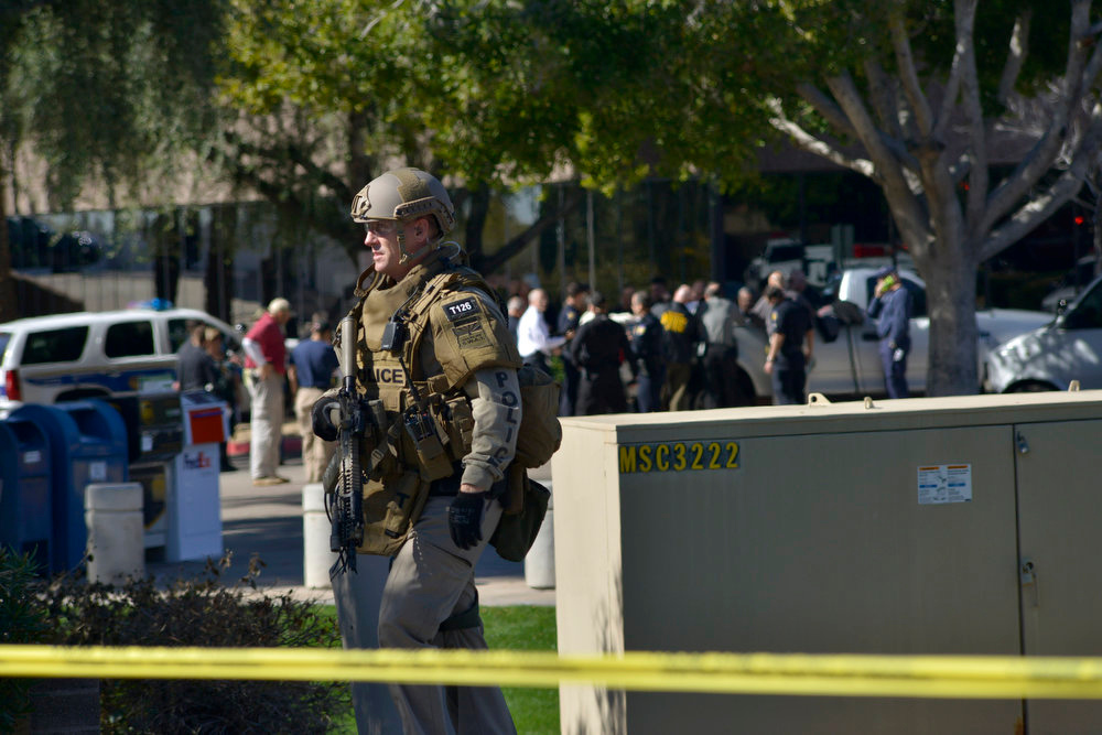 . A SWAT police officer leaves the scene after inspecting an office building after a shooting at the building in Phoenix on Wednesday, Jan. 30, 2013.  A gunman opened fire at a Phoenix office building on Wednesday, wounding three people, one of them critically, authorities said.  (AP Photo/Patrick Sison)