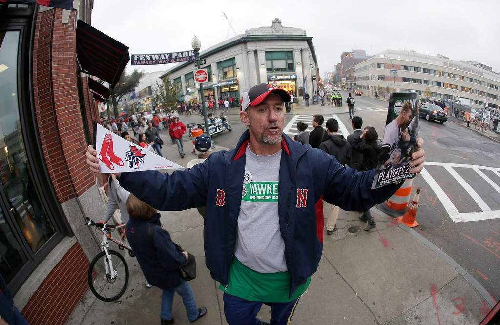 . Clifton Fitzgerald hawks programs and souvenirs outside Fenway Park before Game 1 of the American League baseball championship series between the Boston Red Sox and the Detroit Tigers Saturday, Oct. 12, 2013, in Boston. (AP Photo/Matt Slocum)