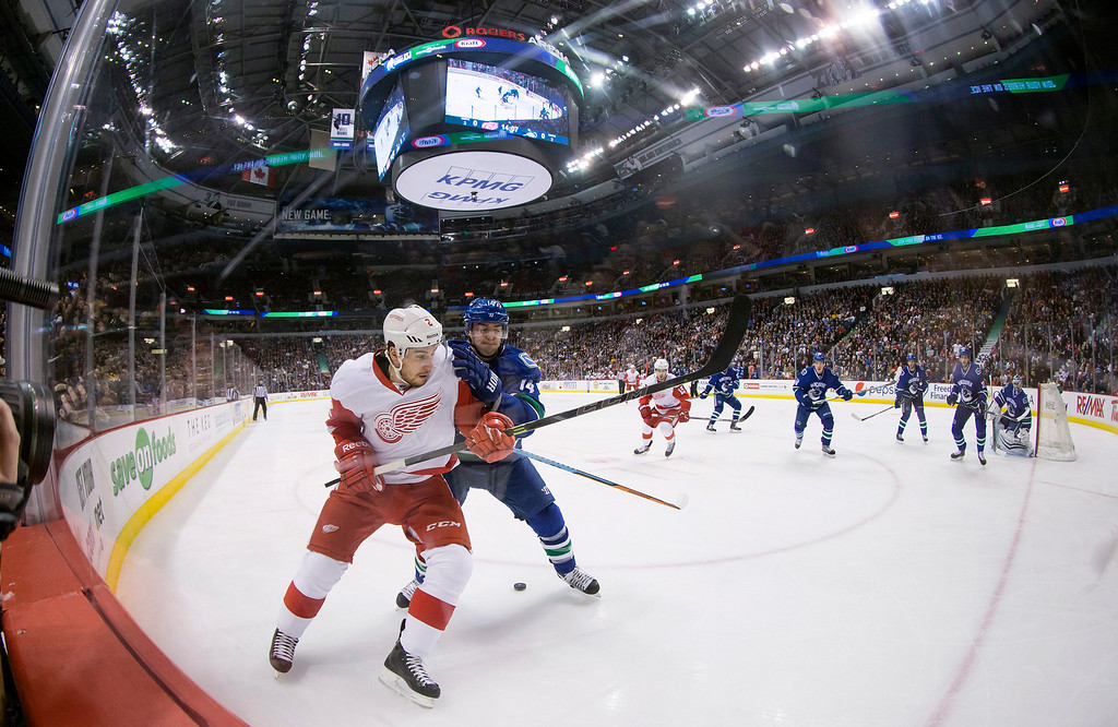 . Vancouver Canucks\' Alex Burrows, second left, checks Detroit Red Wings\' Brendan Smith during the first period of an NHL hockey game in Vancouver, British Columbia on Saturday, Jan. 3, 2015. (AP Photo/The Canadian Press, Darryl Dyck)