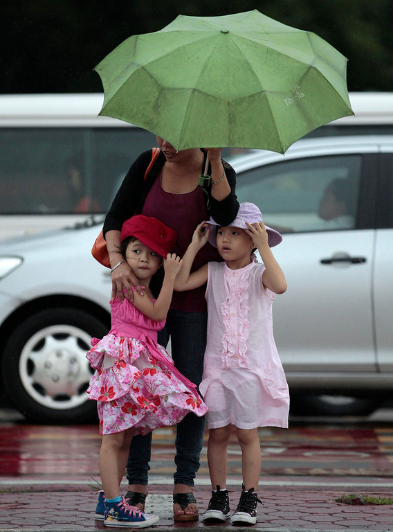 . Two Filipino girls stay close to their mother to keep dry as they cross a road during rain in Manila, Philippines on Sunday, Aug. 11, 2013. More than 3,000 passengers were stranded on piers in the northeastern Philippines Sunday, as Typhoon Utor approaches and prompted authorities to suspend ferry services and warn people to brace for possible flash floods and landslides.   (AP Photo/Aaron Favila)