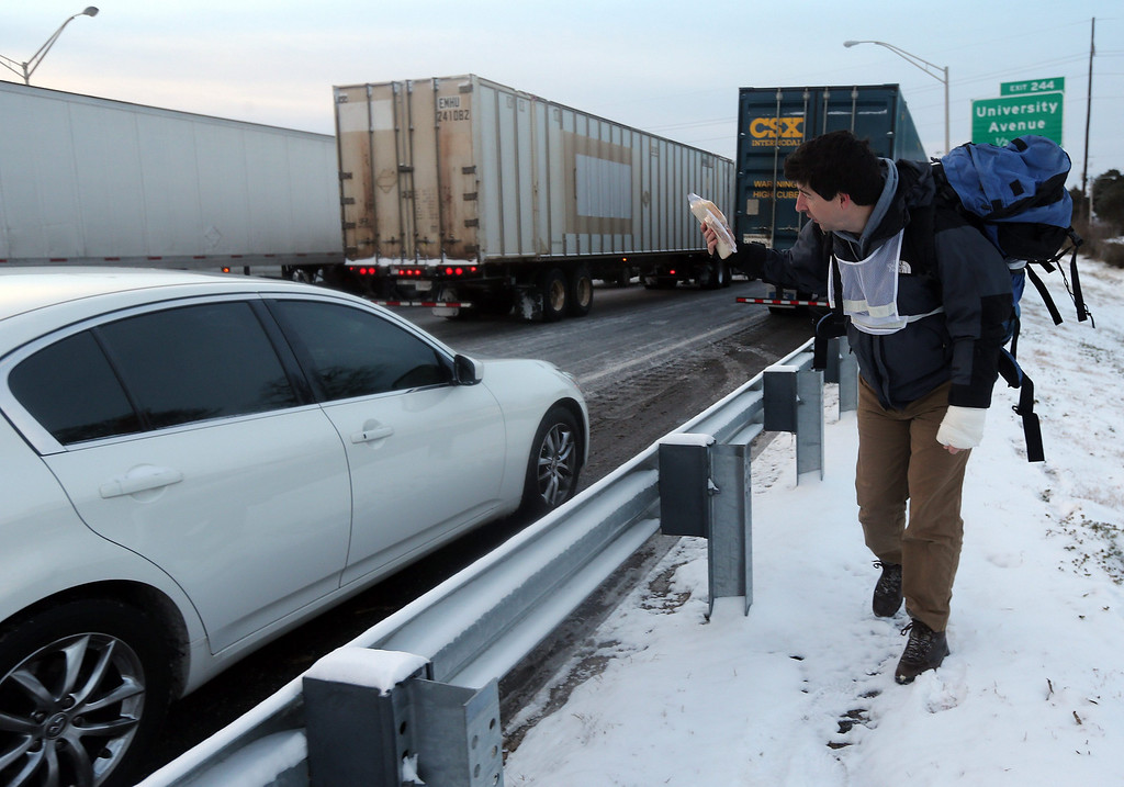 . Matthew Miller walks along the Interstate 75-85 offering peanut butter and jelly sandwiches and hot drinks to motorists stuck in early morning traffic in the aftermath a winter storm in unprepared Atlanta, Georgia, USA, 29 January 2014.   EPA/BEN GRAY / ATLANTA JOURNAL CONSTITUTION