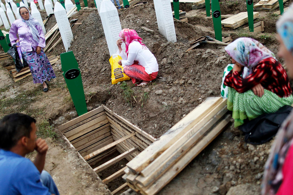 . Bosnian women cry near graves of relatives, where 409 coffins of newly identified victims of the 1995 Srebrenica massacre will be lowered into, in Potocari Memorial Center, near Srebrenica July 11, 2013. The bodies of the recently identified victims will be transported to the memorial centre in Potocari where they will be buried on July 11 marking the 18th anniversary of the massacre in which Bosnian Serb forces commanded by Ratko Mladic killed up to 8,000 Muslim men and boys and buried them in mass graves. REUTERS/Dado Ruvic