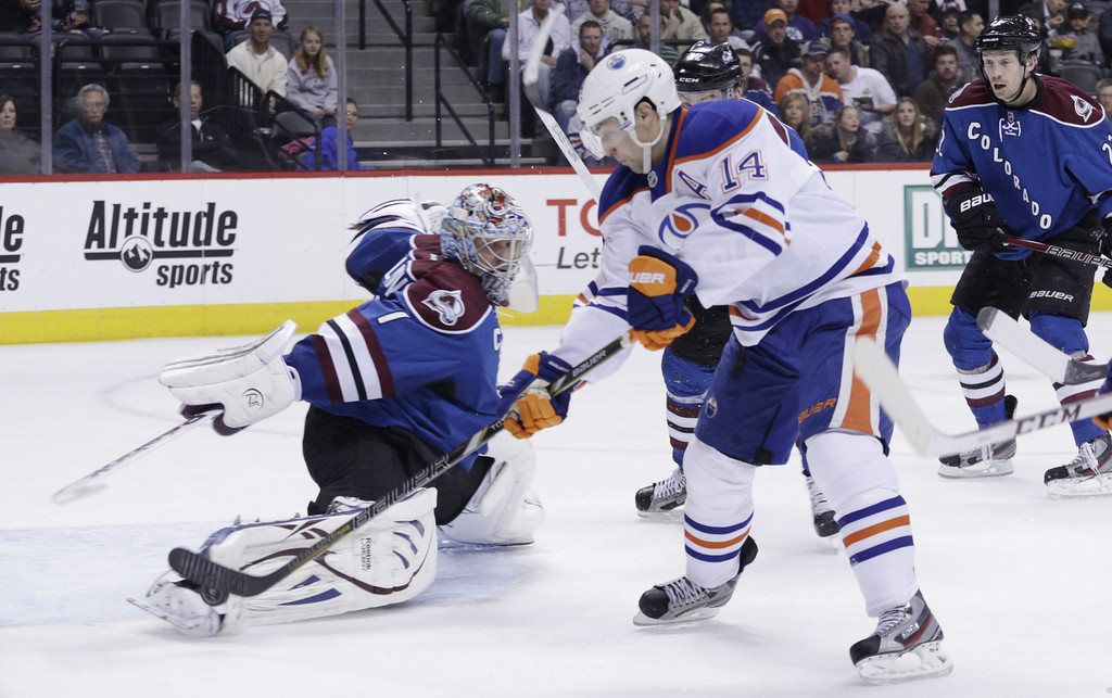 . Edmonton Oilers center Jordan Eberle (14) lifts the puck over the skate of Colorado Avalanche goalie Semyon Varlamov (1) for a goal in the second period of an NHL game on Friday, April 19, 2013, in Denver. (AP Photo/Joe Mahoney)