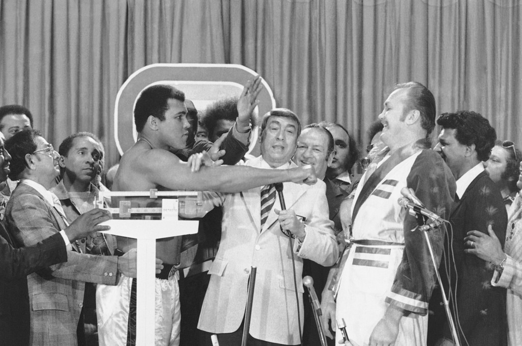 . Muhammad Ali, left, heavyweight champ hams it up with challenger Chuck Wepner during weigh-in at Cleveland Coliseum on Sunday, March 23, 1975 at Richfield, Ohio.   Wepner meets Ali in a scheduled 15-round title bout Monday Center is TV commentator Howard Cosell. (AP Photo)