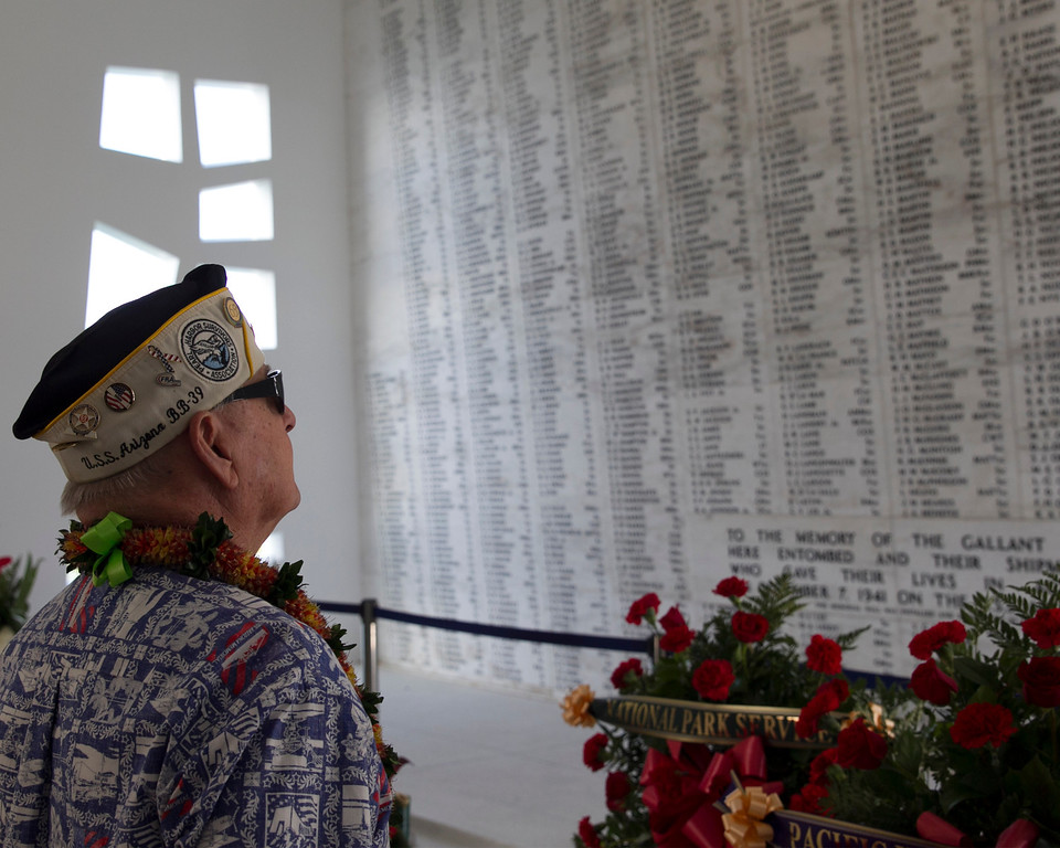 . Pearl Harbor survivor Lou Contor stares at the names on the memorial room aboard the USS Arizona Memorial during the ceremony commemorating the 72nd anniversary of the attack on Pearl Harbor, Saturday, Dec. 7, 2013, in Honolulu.  (AP Photo/Marco Garcia)