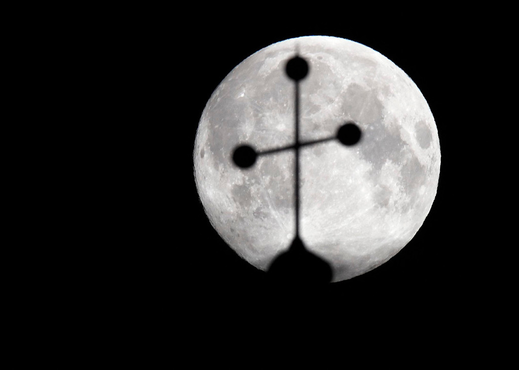 ". A ""super moon\"" is seen behind the cross of a church in Vienna, Austria on June 23, 2013. The largest full moon of the year called a \""super moon\"" will light up the night sky this weekend.  REUTERS/Heinz-Peter Bader"