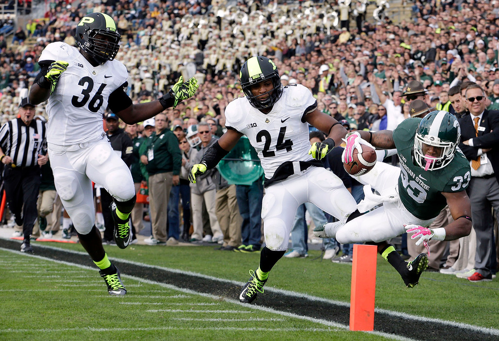 . Michigan State running back Jeremy Langford (33) gets forced out of bounds at the one yard line by Purdue defensive back Frankie Williams (24) during the second quarter of an NCAA college football game in West Lafayette, Ind., Saturday, Oct. 11, 2014. Purdue linebacker Danny Ezechukwu (36) trailed the play. (AP Photo/AJ Mast)
