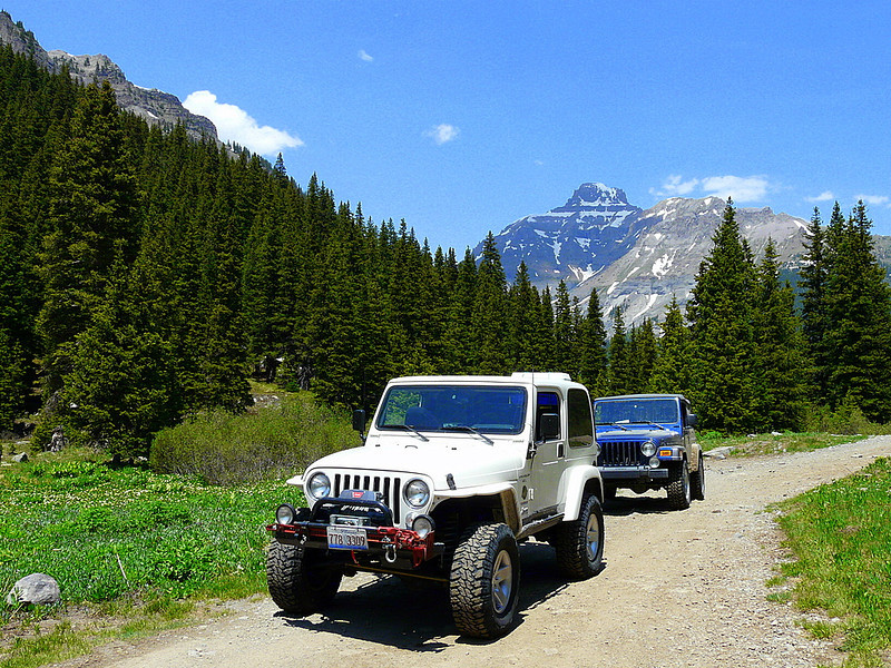 A white jeep and blue jeep drive on a dirt road surrounded by tall mountains.