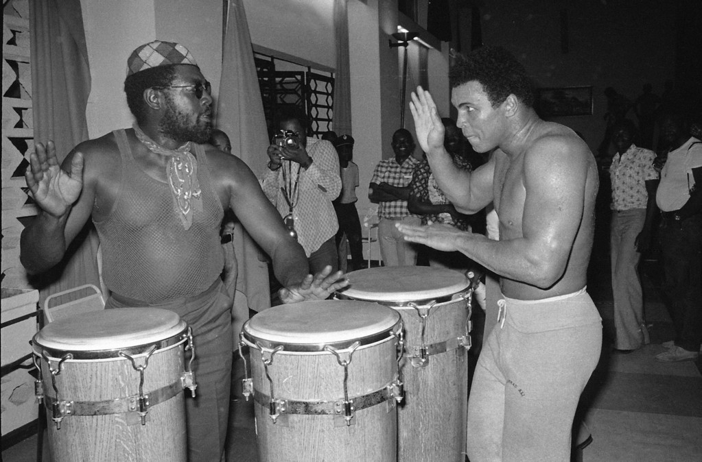 ". Heavyweight contender Muhammad Ali plays the bongos with ""Big Black\"" at a gym in the N\'Sele training center in Zaire, Oct. 5, 1974.  Ali is training for a bout with George Foreman.  (AP Photo/Horst Faas)"