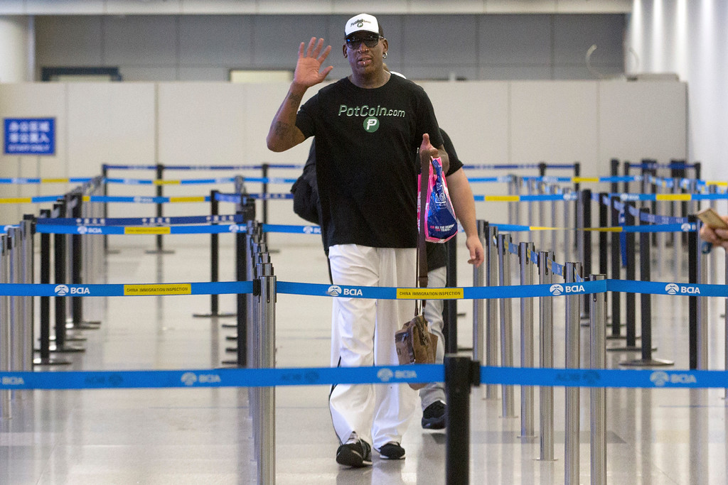 . Former NBA basketball player Dennis Rodman gestures to photographers as he prepares to go through immigration at Beijing Capital International Airport in Beijing, Tuesday, June 13, 2017. North Korea is expecting another visit by Rodman on Tuesday in what would be his first to the country since President Donald Trump took office. (AP Photo/Mark Schiefelbein)