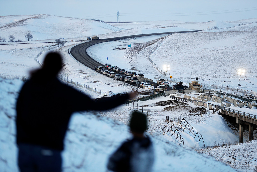 . Law enforcement vehicles line a road leading to a blocked bridge next to the Oceti Sakowin camp where people have gathered to protest the Dakota Access oil pipeline in Cannon Ball, N.D., Saturday, Dec. 3, 2016. (AP Photo/David Goldman)